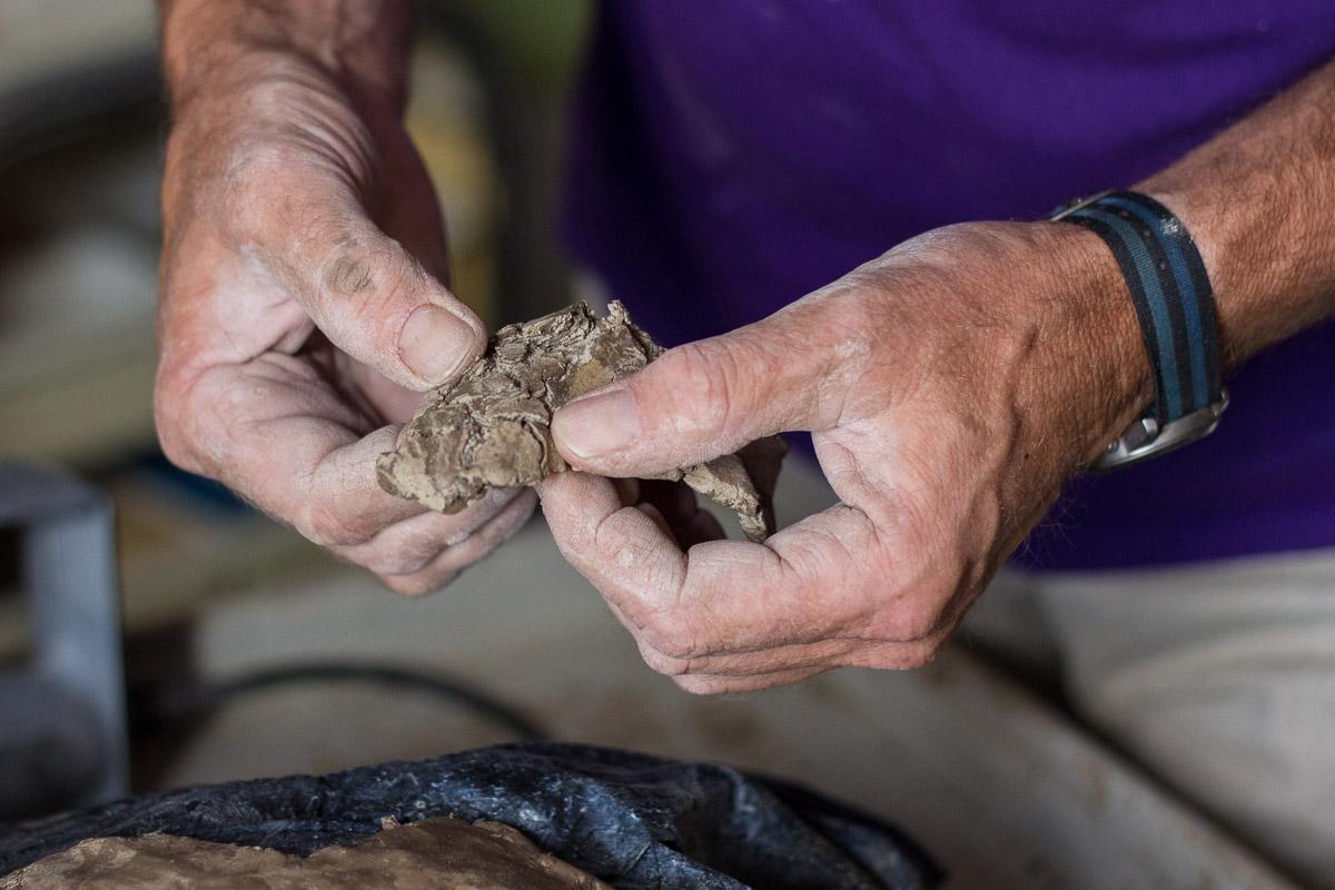 De klei wordt handmatig gemengd en in kleine stukken verwerkt