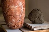 De grondstof klei, uit Ellewoutsdijk, en de vaas ernaast na het bakken heel anders van kleur!
